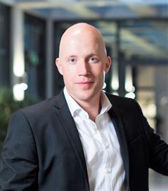Dieses Bild zeigt Björn Brünink, ein Mann mit Glatze. Er ist der Leiter der Arbeitsstelle Barrierefreies Studium (ABS) der Hochschule Düsseldorf.