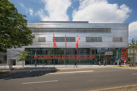 This picture shows building four of the new campus Derendorf of Hochschule Düsseldorf. The front of the building is of glass and steel, indoors you see red elements like the stairs and the walls. This building includes the lecture rooms.