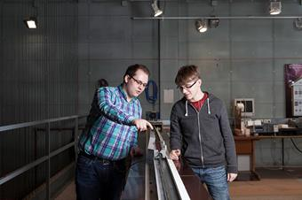 The picture shows two male students in a laboratory of electrical machines.