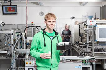 The Picture shows a male student of the Faculty of Electrical and Information Technology in a technical laboratory.