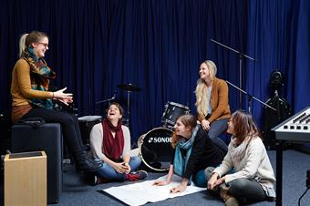 The picture shows a group of female students and a lot of instruments in music studio.