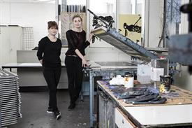 Picture shows two female students in a lab of printing.