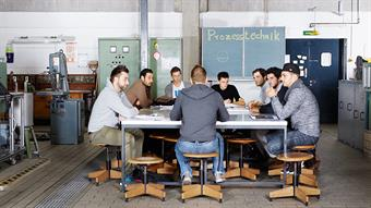 The picture shows a group of male students in a meeting-room of the Faculty of Mechanical and Process Engineering.