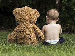 A baby is sitting with his teddy on a meadow