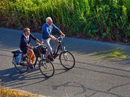 Two elderly people go on a bike ride