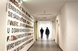 Two students are walking down a bright hallway of HSD. The left wall is decorated with lettering made of different materials.