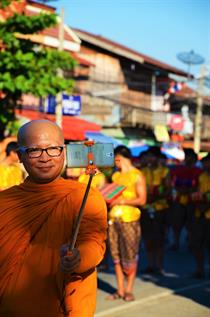 A smiling bold monch, who is wearing a bright orange robe, is taking a Picture of himself and a Parade in the backround with a Selfie-stick.