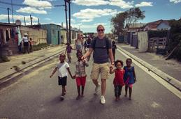 In the background blue sky. Left and right of a small street are colourful huts. In the middle of the street a young man with sunglasses is walking. At each of his hands, he has 2  little children at his hands.