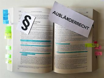 A heavy volume with law Texts lies open. Some sentences are marked and many pages are marked with post-ist. A paragrph sign and the word Ausländerrecht (Aliens Law) are spread over the book.