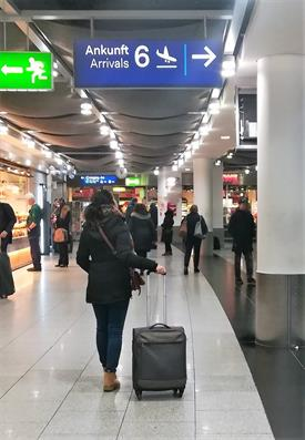 A Young woman dressed in dark clothes and a suitcase is at the Airport. She is Standing below a blue sign which has the word Arrival written on it. She is looking up towards the sign.