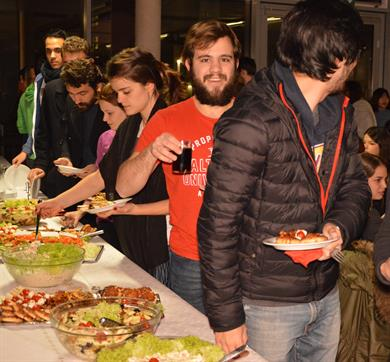 International students are loading different dishes onto their plates at a diverse buffet.