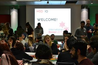 Many international students are seated at tables and talking to each other. In the Background there is a presentation projected onto the wall which says Welcome International Dinner 2017.