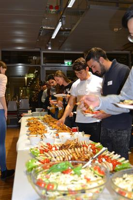 A Long table is filled with salads and different finger Food dishes. International students are Standing in line along the table and filling their plates with Food.
